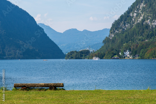View of the Alpine lake among the mountains in Hallstatt with green lawn with bench