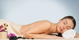 Beautiful young woman relaxing with stone massage at beauty spa - 219993601