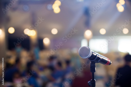 microphone in concert hall or conference room soft and blur style for background.Microphone over the Abstract blurred photo of conference hall or seminar room background. - 219994494