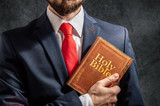Man looks like politician or businessman stands with holy bible - 219995683