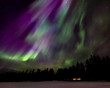 Aurora over cabin in the forest