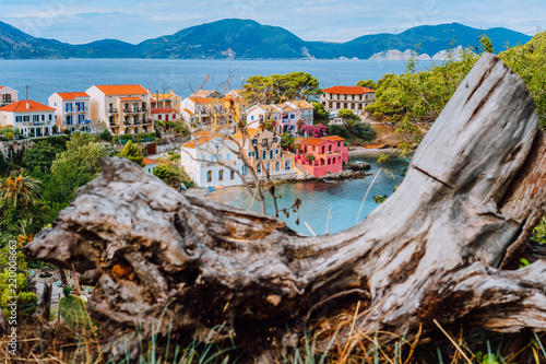 Foto Murales Assos village in Kefalonia, Greece. Calm blue bay water and colored traditional houses. Old snag in the front