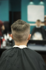 Rear view of boy in barber shop for his hair done styled