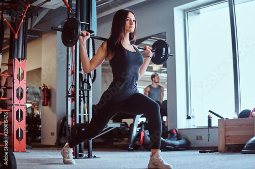 Piękna brunetki kobieta w sportswear robi lonży z barbell w sprawności fizycznej klubie lub gym.