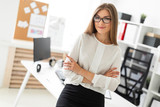 A young girl is standing leaning on a table in the office. - 220016038
