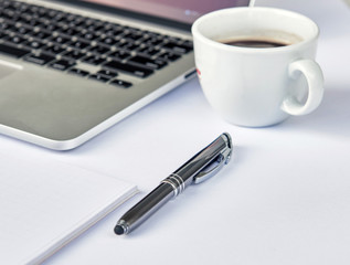 White office desk table with blank notebook, laptop computer, pen and cup of espresso coffee. Working desk table concept. Top business view.