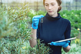 Agronomist woman holding a soil sample and a tablet. Concept environmentally friendly farm production - 220024442