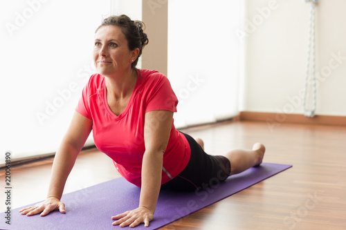 Naklejka Smiling woman on purple mat doing upward facing dog yoga pose. Pretty female yogi practicing urdhva mukha svanasana in studio. Exercise, pilates, workout, sport outfit, healthy lifestyle concepts