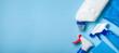Cleaning supplies - bottles, sprays sponge on bright pastel background