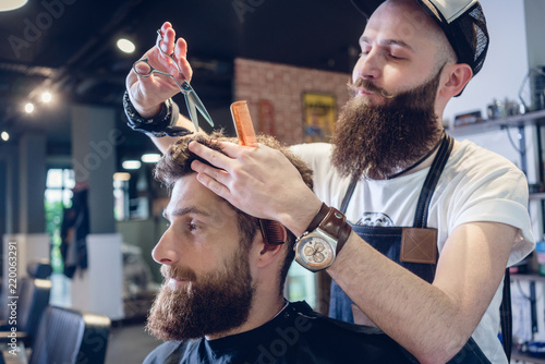 Fototapeta samoprzylepna Dedicated male hairstylist using scissors and plastic comb while giving a cool haircut to a redhead bearded young man in a trendy beauty salon
