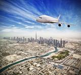 Huge commercial jetliner flying above Dubai city, UAE. - 220063832