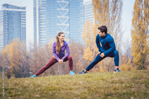 Leinwanddruck Bild Sport couple doing warm-up exercise before starting a run to become more fit