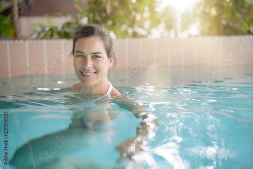Atrakcyjna brunetki kobieta relaksuje w zdroju basenie