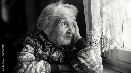 Leinwandbild Motiv Elderly woman in the house sitting at the table looking out the window. Monochrome photo.