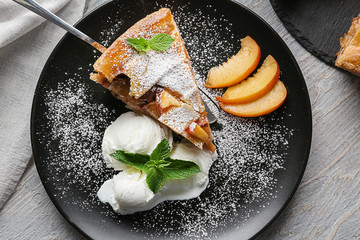 Plate with piece of tasty homemade peach pie and ice-cream on table
