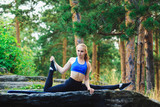 Blonde woman doing quad stretching sitting on the splits outdoors on a rock in the forest. Yoga nature concept.