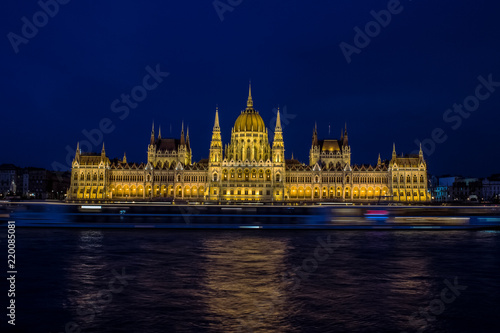 long exposure photography beautiful concept of Budapest parliament buildings architecture symmetry facade on riverfront shore with fuzzy illuminated cruise ship