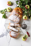 Homemade sliced puff pastry apple strudel pie on cooling rack served with ripe fresh apples, branches, cieve and sugar powder over white marble texture background. Flat lay, space - 220086436