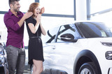 Handsome husband surprising his wife with a car purchase - 220099866