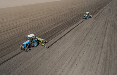 Aerial view of two blue tractors plows the earth in field on a summer day against a black earth background. Agriculture. Two tractors travel one after another along the black field © LALSSTOCK