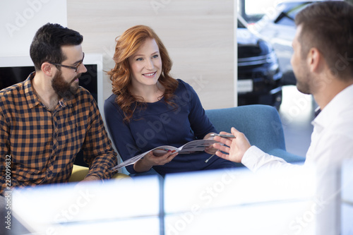 Couple looking at car offer and talking to a dealer in a car showroom - 220099832