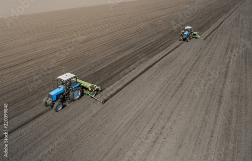 Aerial view of two blue tractors plows the earth in field on a summer day against a black earth background. Agriculture. Two tractors travel one after another along the black field