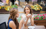 communication, friendship and people concept - happy young women drinking coffee at outdoor cafe - 220107882