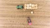 aerial view of tractor stacking harvested hay bales on a flat bed trailer - 220109233
