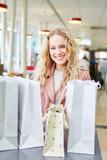 Glückliche Kundin mit vielen Einkaufstüten - 220109296