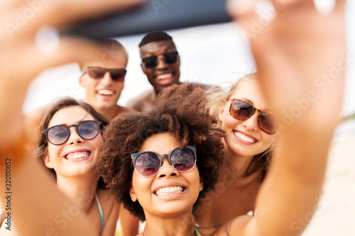 friendship, summer holidays and people concept - group of happy friends taking picture by smartphone on beach