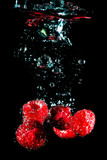 Closeup shot of ripe raspberry covered with air bubbles and falling down in water on black background