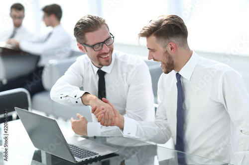 handshake of the employees sitting behind a Desk