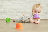 Baby girl playing on the floor with plastic educational   cups, early learning concept - 220167608