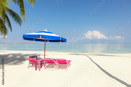 Leinwanddruck Bild Pink beach Chairs And blue Umbrella In Palm Beach - Tropical Holiday concept