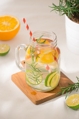 Infused water with lime, orange, apple and rosemary. Cold refreshing detox summer drink .Selective focus