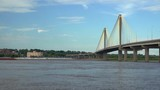 A long tow on the Mississippi River is approaching the  Clark bridge at Alton, 8x fast speed. - 220186406