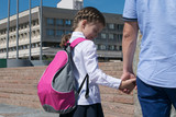 Dad is holding the hand of a girl with a backpack to school
