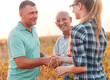 Handshake for deal, group of farmers standing in a field examining soybean crop before harvesting.