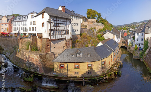 Leinwandbild Motiv waterfall in the city center of Saarburg, Germany surrounded by houses on a hill