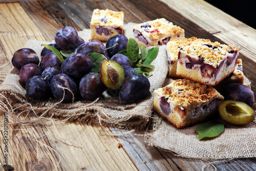 Rustic plum cake on wooden background with plums around. - 220200270