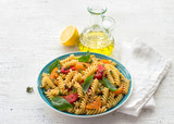 Summer pasta with tomatoes, herbs and olive oil on a light background. Delicious healthy diet - 220204839