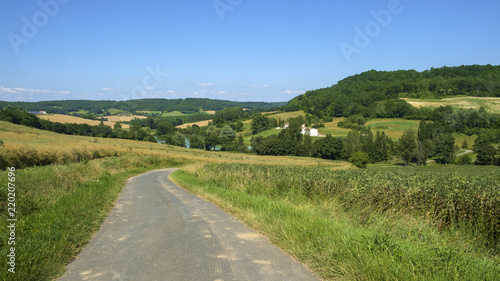 Fototapeta A country lane winds through rolling countryside near Frespech on a sunny early summer afternoon in rural Lot et Garonne, France