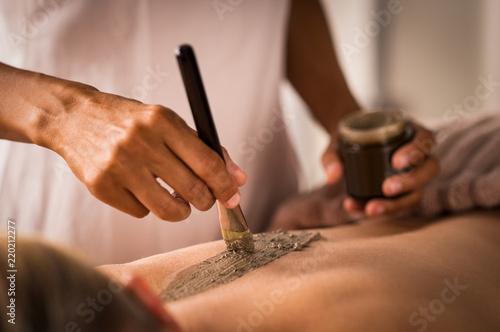 Leinwanddruck Bild Beautician applying mud on body