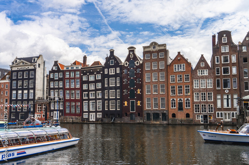 Row of authentic canal houses and touboats in Amsterdam, Netherlands