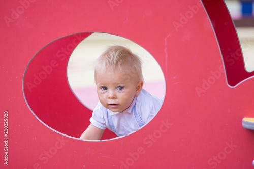 Leinwandbild Motiv Adorable baby boy, playing with different rides on the playgdorund