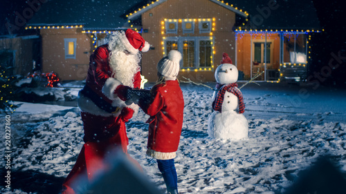 magical new year evening authentic santa claus gives cute little girl a wrapped gift box