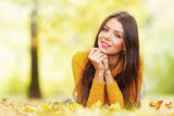 Cute woman laying in autumn park - 220238089