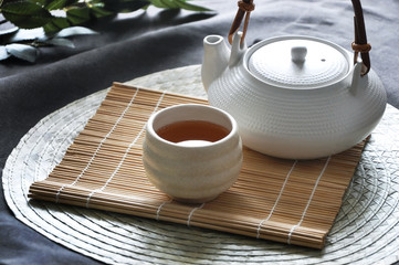 Teapot with a Cup of Hot Tea