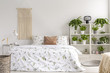 Close to nature bright bedroom interior with many green plants beside a big bed. Woven tapestry above the bed. Real photo.