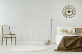 Gold clock above bed with blanket in white bedroom interior with chair and dandelion. Real photo